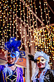 Women in costume and mask at the Venice Carnival 2019, lights and bokeh in background. Venice, Veneto, Italy