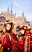 Man and woman in costume and mask at the Venice Carnival, Piazza San Marco (St. Mark's Square), Venice, Veneto, Italy