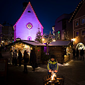 a child is warming in front of a bonfire by the Christmas market in Val Gardena, Bolzano province, South Tyrol, Trentino Alto Adige, Italy