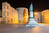 View of a statue, the Torre Alfonsina and the old walls of Otranto at night. Province of Lecce, Salento, Apulia, Italy, Europe.