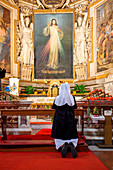 A nun prays inside the Church of the Holy Spirit in the Saxon District Europe, Italy, Lazio, Province of Rome, Rome