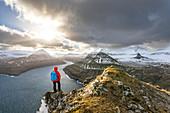 Hiker standing on peak over Funningur fjord (Eysturoy island, Faroe Islands, Denmark) (MR)