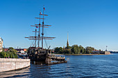 Old nautical vessel on Neva River with Peter and Paul fortress in the background. Saint Petersburg, Russia.