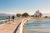 Tourists walking on the bridge that link Elafonissos island with the orthodox church of St. Spyridon, Elafonissos, Laconia region, Peloponnese, Greece, Europe