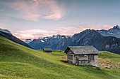Alpine huts with snowy peaks in the background, Tombal, Soglio, Bregaglia Valley, canton of Graub?nden, Switzerland, Europe