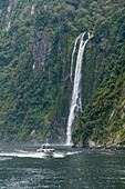 Touristic boat and Stirling Falls in Milford Sound. Fiordland NP, Southland district, Southland region, South Island, New Zealand.