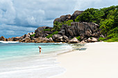 A young lady strolling along Grand Anse. La Digue island, Seychelles, Africa