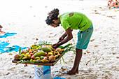 Local man preparing a plate of fresh tropical fruits. Praslin island, Seychelles, Africa