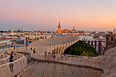 Tourists on the curved footbridge of Metropol Parasol at sunset, Seville, province of Seville, Andalusia, Spain