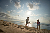 Boy and girl are running down the dune, Dune d'Arcachon, French Atlantic Coast, Aquitaine, France