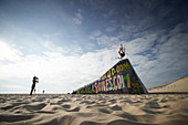 Young people jump from half sunken bunker on the beach, Cap Ferret, French Atlantic coast, Aquitaine, France