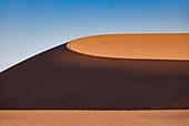 Ein Mann lüft auf einer Düne in der Wüste Namib, Namib Naukluft Park, Namibia