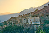 The village Oumesnat shortly after sunset at the foot of steep mountains, Valley of Ammeln in Anti Atlas, Morocco
