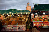 A stand with dried fruit and dates, juice stand with fruit in front of the minaret of a small mosque, Jemaa El Fna, Marrakech, Morocco