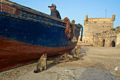 Two cats in front of fishing boat and man in front of fortress tower in the harbor of Essaouira, Atlantic Coast, Morocco
