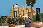 Men paint a wall in El Kelaâ M'Gouna with a kashbah, Dadestal High Atlas, Morocco