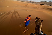 Camel is led by Berber through dunes, in the dune area Erg Chebbi, Tafilalet, Morocco