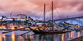 Rabelo boats with port wine barrels on the banks of the Douro at dusk, Porto, Portugal