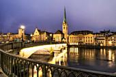 Zürich an der Limmat in der Abenddämmerung, Stadthaus, Fraumünster und Münsterbrücke, Schweiz