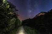 Dimly lit path leads towards the starry sky