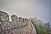 Steep stairs, wall and fortified tower in the fog in Castelo dos Mouros Sintra, Lisbon, Portugal