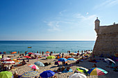People on the beach next to the fortress in Sesimbra on the Setubal Peninsula, south of Lisbon, Portugal