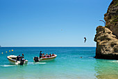 Man jumps from rocks at the beach of Benagil, Algarve, Portugal