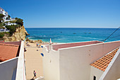 View between houses to the beach in bright blue sky in Carvoeiro, Lagoa, Algarve, Portugal