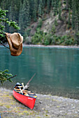 Wet straw hat hangs from a tree, in the background a canoe on the shore, break at the Yukon River, Yukon, Canada
