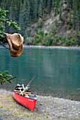 Nasser Strohhut hängt an einem Baum, im Hintergrund ein Kanu am Ufer, Pause am Yukon River, Yukon, Kanada