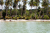 Tourists at the palm-lined, tropical dream beach, A Na Lay Resort, Koh Kood, Koh Kut, Trat, Thailand