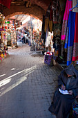 Salesman with traditional garment in front of his business in the alleys of the souq of Marrakesh, Marrakech, Morocco