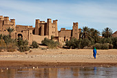 Bedouin in front of the walls of the Kasbah Ait Ben Haddou and the desert, Ait Ben Haddou, Morocco