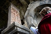Tourist reads a guide in front of an ancient Christian stele, Haghpat monastery near Alverdi, Caucasus, northern Armenia, Asia MR: Andrea Seifert