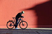 Young man with bicycle in urban environment, Munich, Bavaria, Germany
