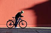 Junger Mann mit Fahrrad in urbaner Umgebung, München, Bayern, Deutschland