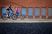 Young couple on eBikes in urban environment, Munich, Bavaria, Germany