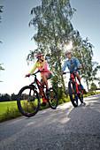 Junge Frau und junger Mann auf eMTB, Münsing, Bayern, Deutschland