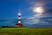 Full moon breaks through the clouds at the lighthouse Westerhever, North Sea, Schleswig-Holstein, Germany