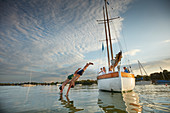 Two teenagers jump from the TWINSTER SIR SHACKLETON ON THE AMMERSEE, Ammersee, Bavaria Germany * Lake Ammer, Bavaria, Germany