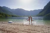 Zwei Mädchen klatschen sich ab, SUP, Bohinjer See, Triglav Nationalpark, Slowenien