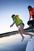 2 girls jump aboard a sailboat with life jackets, Bay of Tomozina, Cres, Croatia