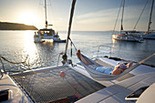Skipper Rudi, hammock, catamaran EOS, at buoy island Susak, Kvarner bay, Adriatic sea, Croatia