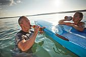 Pause am SUP Board, Mann und Frau trinken Bier im Starnberger See, Bayern, Deutschland