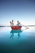 Füße auf der Bordwand, Entspannung in einem Ruderboot auf dem Wörthsee, Bayern, Deutschland