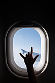 Silhouette of girl's hand gesturing by airplane window