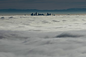 Silhouetted skyscraper buildings above clouds, Vancouver, British Columbia
