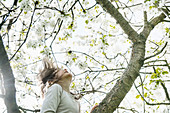 Carefree girl climbing spring apple blossom tree