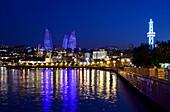 Evening view from the waterfront over Baku Bay to the Flame Towers with illumination, Baku, Caspian Sea, Azerbaijan, Asia