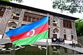 Flag of Azerbaijan and facade of the historic Xan Sarayi Fortress in Sheki, Azerbaijan, Asia